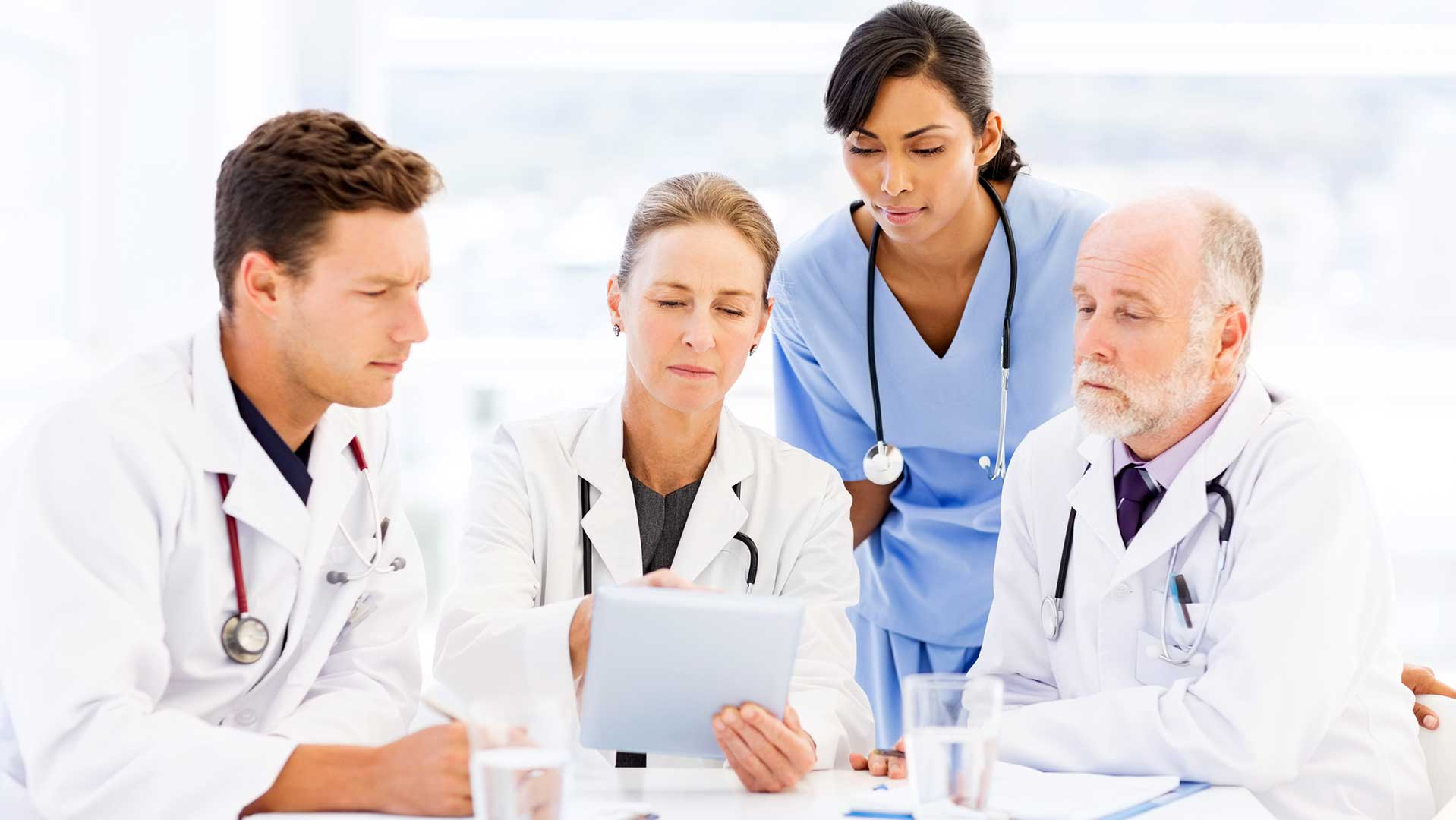 three doctors and a nurse looking at soem data on a tablet