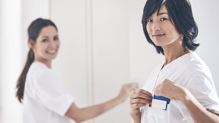two female nurses in a changing room smiling