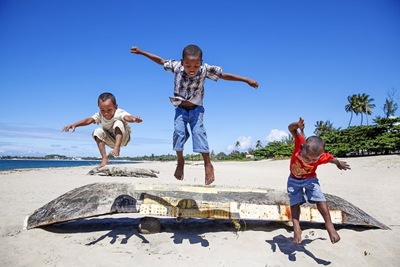 three boys jumping over a boat by a sea shore smiling