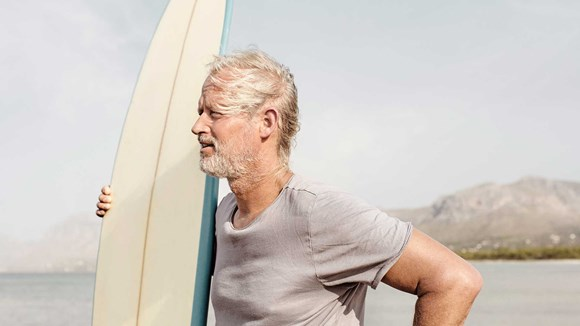 a middle-aged man on a shore holding a surf board